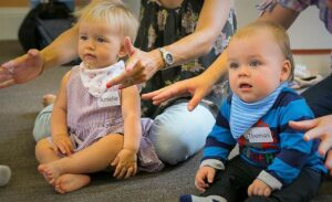 Grown-ups signing ALL GONE as babies watch their tutor